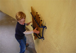 kid playing chimes in tunnel